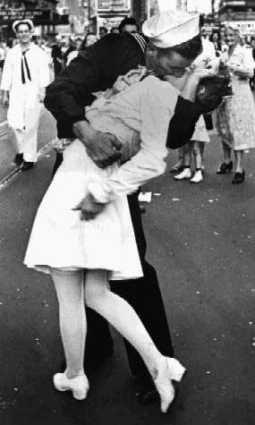 V-J Day in Times Square, a photograph by Alfred Eisenstaedt, was published in Life in 1945 with the caption, A nurse clutches her purse and skirt as a sailor kisses her in Times Square